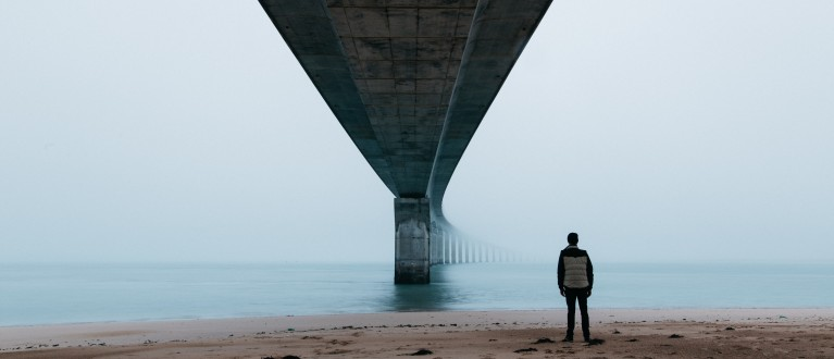 man standing under a bridge